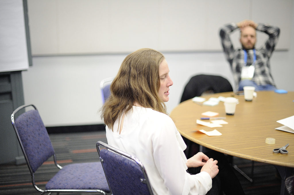 Portrait of Cynthia Bennett, a PhD student working on accessibility and design. She is seated on a purple chair at a round table.